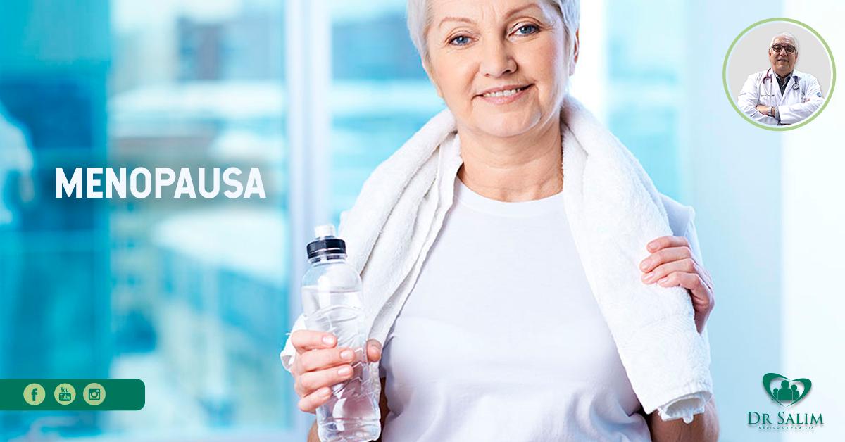 A imagem mostra uma mulher de meia idade, aparentemente com 40 anos, do abdome ao rosto, segurando uma garrafa de água e uma toalha em volta do seu pescoço.